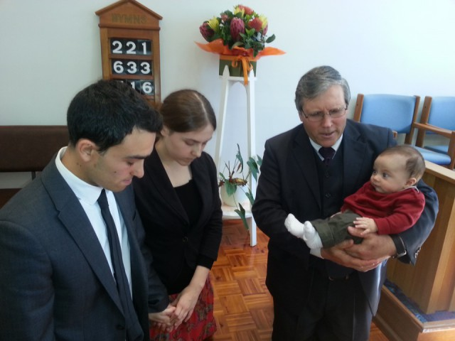 Pastor Matthias Thiel praying with Nadine, Domenic and baby Immanuel